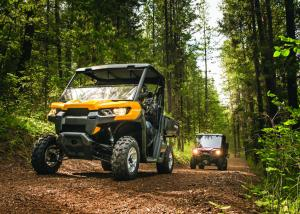 2016.can-am.defender.yellow.front.riding.on-trail.jpg